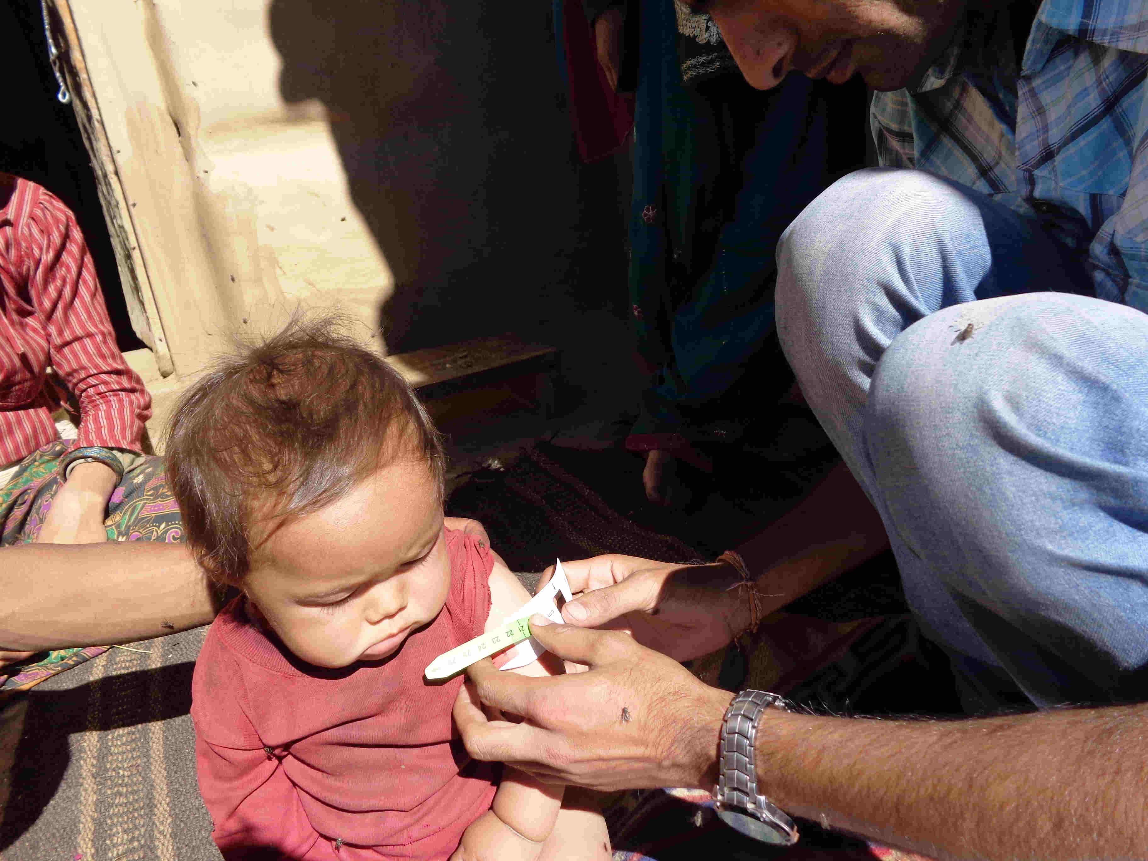Measuring MUAC of child @ Pahada VDC